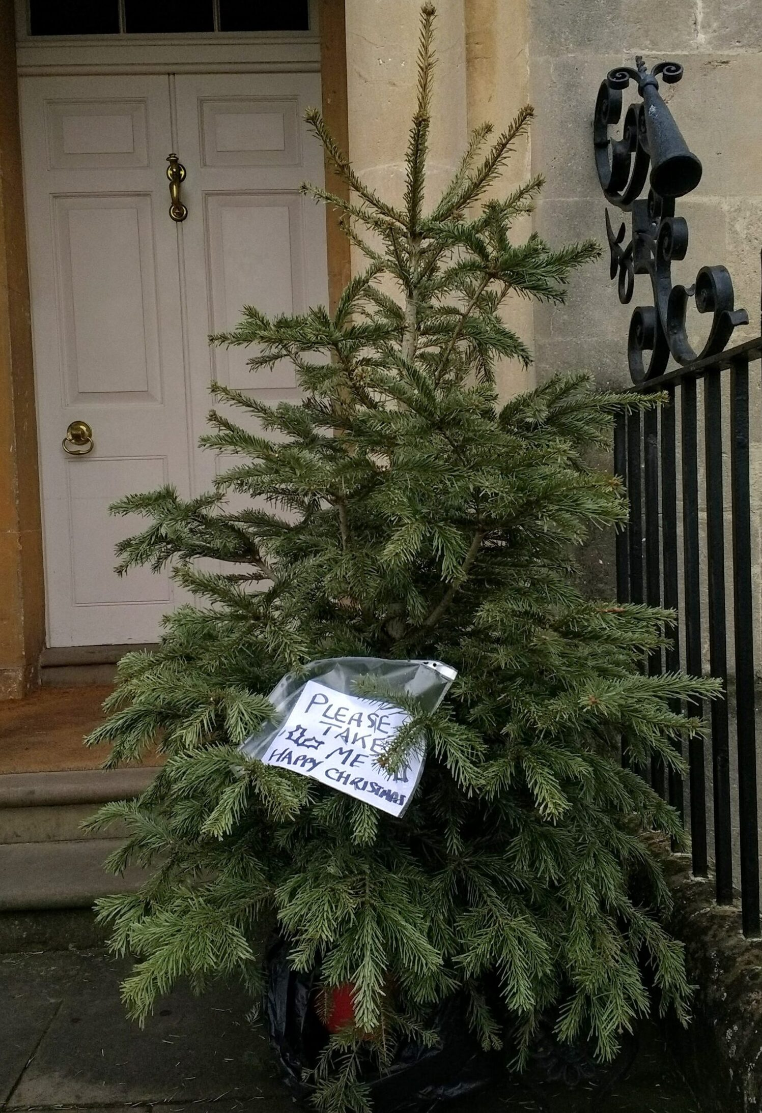 Please Take Me note on Christmas tree outside fancy doorway